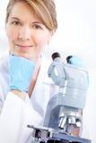Vrouw met microscoop stock afbeeldingen