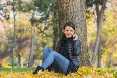 Vrouw met Mobiel in een Bos in de Herfst stock fotografie