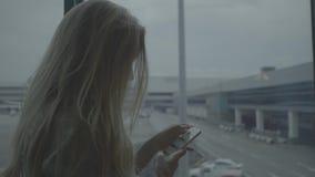 Vrouw met mobiele telefoon bij de luchthaven stock footage