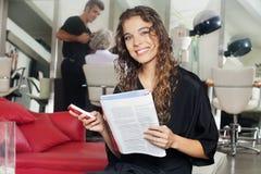 Vrouw met Mobiele Telefoon en Tijdschrift bij Haarsalon stock afbeeldingen