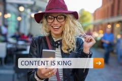 Vrouw met mobiele telefoon in handen het glimlachen De inhoud is koning stock fotografie