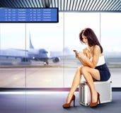 Vrouw met mobiele telefoon in luchthaven royalty-vrije stock fotografie