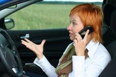 Vrouw met mobilein een auto. stock foto