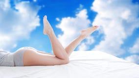 Vrouw met mooie benen op een vage hemelachtergrond met wolken royalty-vrije stock afbeeldingen