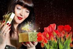 Vrouw met Mooie boeket verse rode tulpen en gift royalty-vrije stock afbeelding