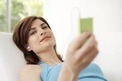 Vrouw met mp4 thuis Stock Afbeelding