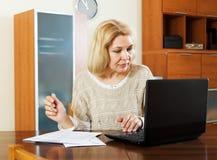 Vrouw met notitieboekje en documenten in bureau Stock Foto