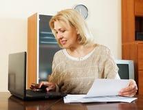 Vrouw met notitieboekje en financiële documenten thuis Royalty-vrije Stock Afbeeldingen