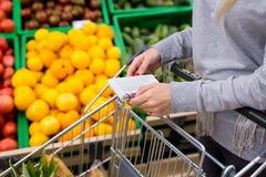 Vrouw met notitieboekje in kruidenierswinkelopslag, close-up Het winkelen lijst op papier stock afbeelding