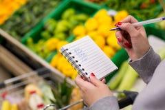Vrouw met notitieboekje in kruidenierswinkelopslag, close-up Het winkelen lijst op papier Stock Afbeeldingen