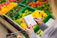 Vrouw met notitieboekje in kruidenierswinkelopslag, close-up Het winkelen lijst op papier Stock Foto