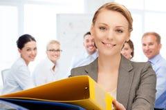 Vrouw met omslagen in bureau Stock Afbeeldingen