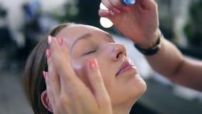 Vrouw met Oogdalingen De close-up van mooi meisje, maakt omhoog meester van toepassing zijnd eyedrops in haar ogen Jong vrouwelij stock video