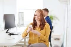 Vrouw met oortelefoons en smartphone op kantoor Stock Foto's