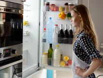 Vrouw met open koelkast stock fotografie