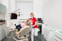 Vrouw met open mond die haar die tanden hebben door de vrouwelijke controle van tandartsTeeth op tandarts` s kantoor worden onder stock foto's