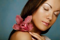 Vrouw met orchideebloem Royalty-vrije Stock Foto's