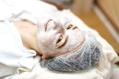 Vrouw met organisch masker op gezicht in kuuroordsalon stock afbeelding