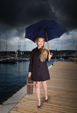 Vrouw met oude koffer en paraplu bij haven stock afbeelding