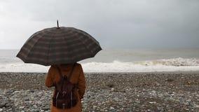 Vrouw met paraplu dichtbij stormachtige overzees stock videobeelden