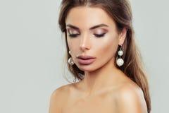 Vrouw met perfecte make-up en parelsoorringen stock afbeelding