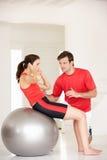 Vrouw met persoonlijke trainer in huisgymnastiek Stock Foto