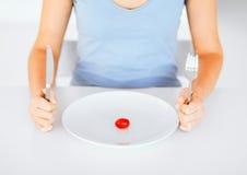 Vrouw met plaat en één tomaat Stock Afbeeldingen