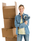Vrouw met Plakband die zich door Gestapelde Kartondozen bevinden Stock Fotografie