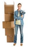 Vrouw met Plakband die zich door Gestapelde Kartondozen bevinden Royalty-vrije Stock Foto