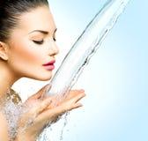 Vrouw met plonsen van water in haar handen Royalty-vrije Stock Afbeeldingen
