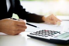 Vrouw met rekeningen en calculator Vrouw die calculator gebruiken aan calcu stock afbeelding