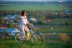Vrouw met retro fiets op de heuvel in de avond Stock Afbeelding