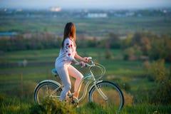 Vrouw met retro fiets op de heuvel in de avond Royalty-vrije Stock Fotografie