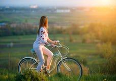 Vrouw met retro fiets op de heuvel in de avond Stock Foto's