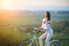 Vrouw met retro fiets op de heuvel in de avond Royalty-vrije Stock Foto's