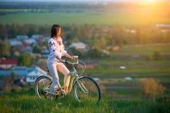 Vrouw met retro fiets op de heuvel in de avond Stock Foto