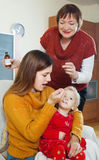 Vrouw met rijpe moeder die voor zieke peuter geven Royalty-vrije Stock Fotografie