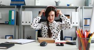 Vrouw met rode hoofdtelefoons op boek sluiten en schouders die terug leunen stock footage