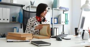 Vrouw met rode hoofdtelefoons op schouders die boek beduimelen en laptop met behulp van stock footage