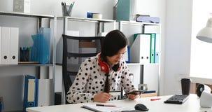 Vrouw met rode hoofdtelefoons op schouders die creditcardaantal ingaan in smartphone stock video