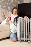 Vrouw met rode kop dichtbij olieverwarmer Stock Foto