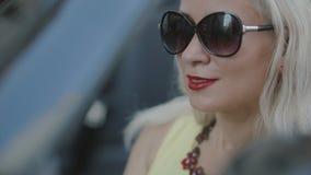 Vrouw met rode lippenstiftzitting in de auto stock videobeelden