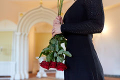 Vrouw met rode rozen bij begrafenis in kerk royalty-vrije stock afbeeldingen