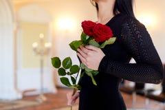Vrouw met rode rozen bij begrafenis in kerk royalty-vrije stock afbeelding