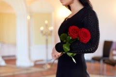 Vrouw met rode rozen bij begrafenis in kerk stock afbeelding