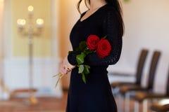 Vrouw met rode rozen bij begrafenis in kerk stock foto's