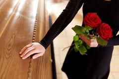 Vrouw met rode rozen en doodskist bij begrafenis stock fotografie