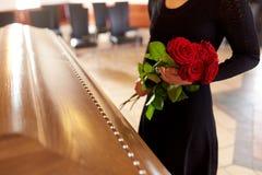 Vrouw met rode rozen en doodskist bij begrafenis royalty-vrije stock afbeelding