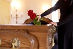 Vrouw met rode rozen en doodskist bij begrafenis royalty-vrije stock foto's