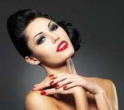 Vrouw met rode spijkers en creatief kapsel Royalty-vrije Stock Afbeeldingen